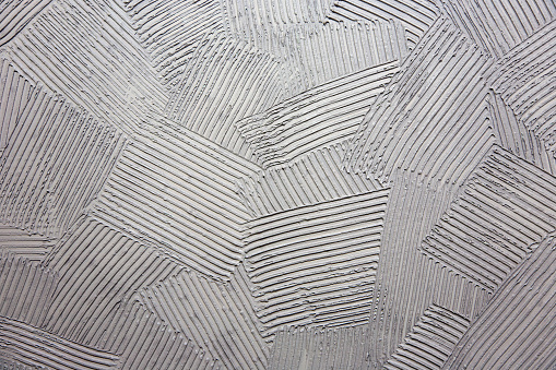 Concrete surface with striped relief and rich texture.