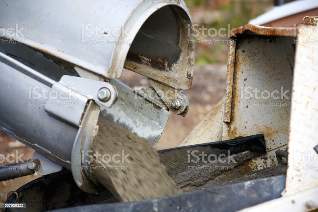 Concrete being poured from a truck into a concrete pump at a...