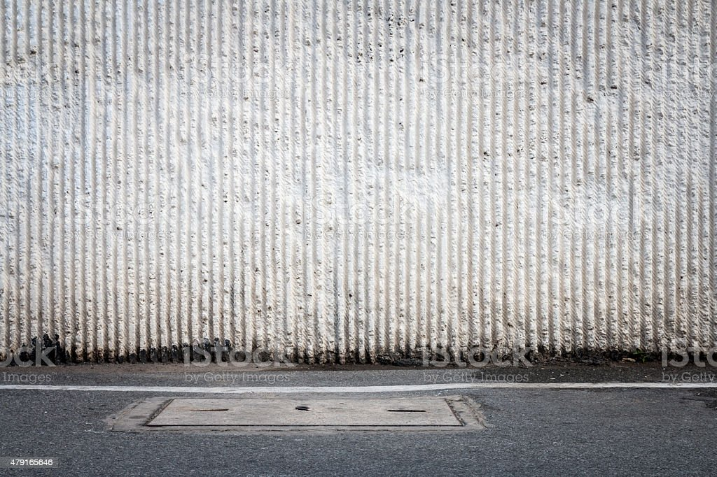 Concrete wall and asphaltic road stock photo