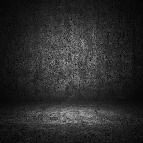 a concrete wall dimly lit surrounded by darkness - dimly stock pictures, royalty-free photos & images