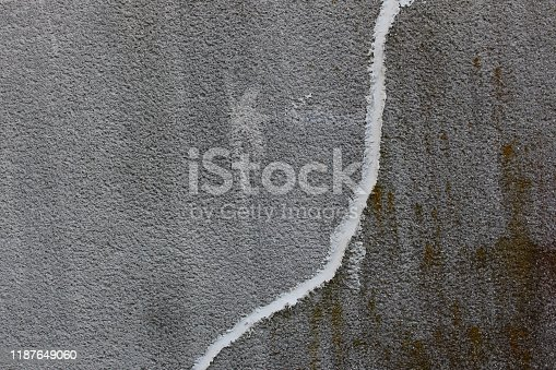 istock Concrete wall with crack repaired with white concrete patching putty 1187649060