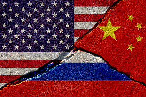 concrete wall with painted united states, china and russia flags