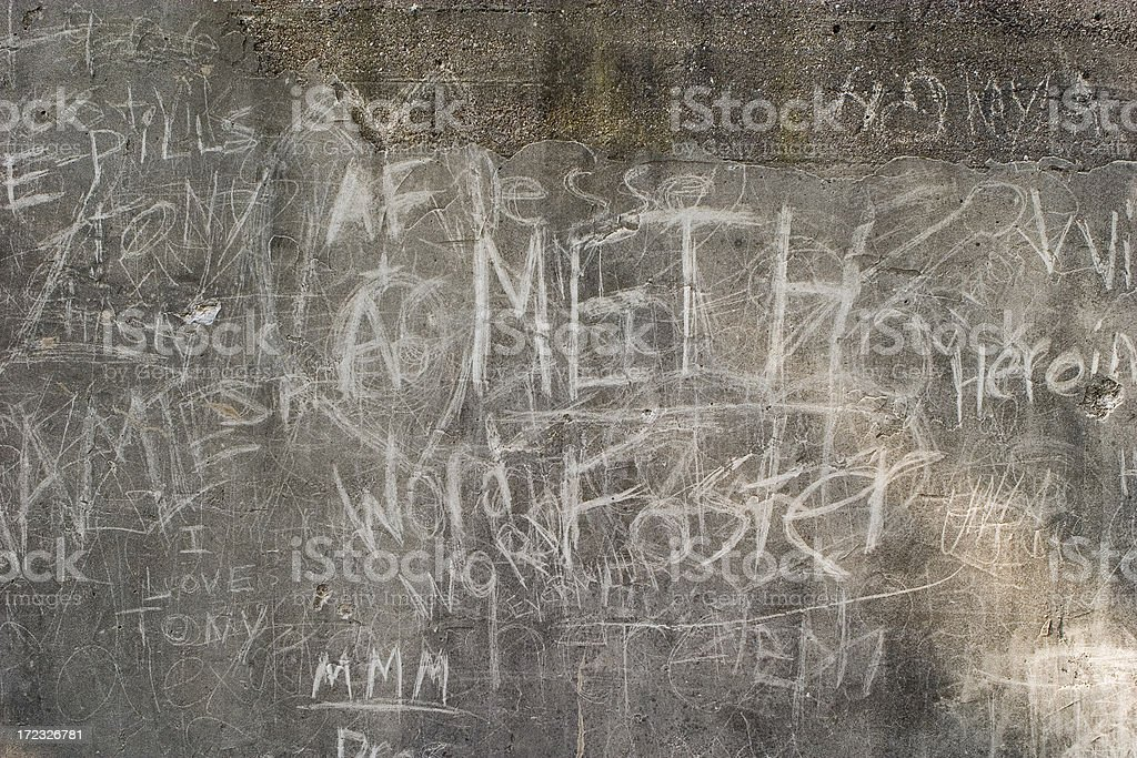 concrete wall with words scratched in stock photo