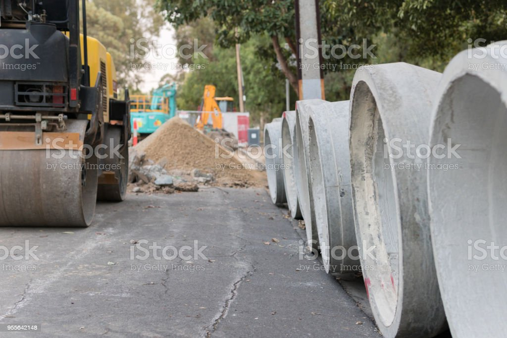Steam roller parked near storm water pipes