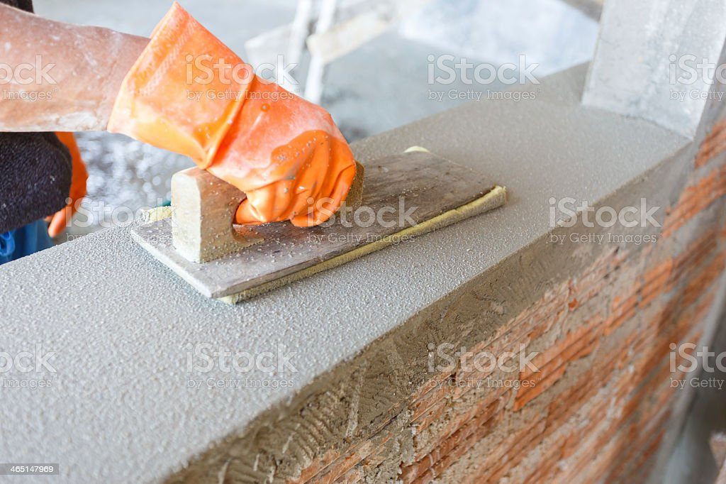 A concrete worker plastering a wall royalty-free stock photo