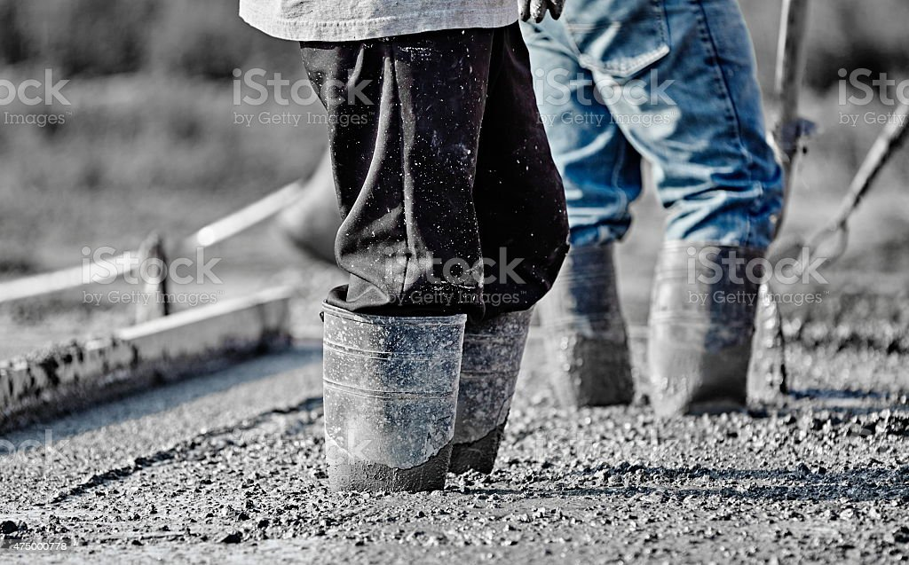 Concrete workers in heavy boots working in new wet concrete. stock photo