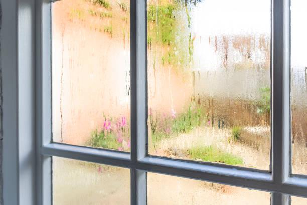 condensation on old window panes - влажный стоковые фото и изображения