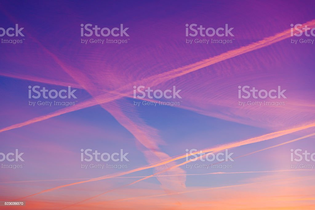 Condensation trails across beautifull sunset sky. stock photo