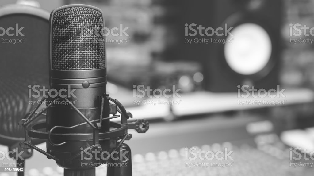 black and white condenser microphone on audio mixing board & studio...