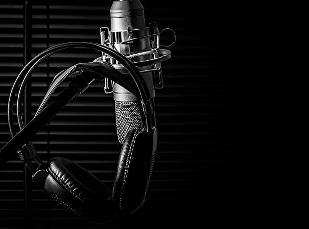condenser microphone on boom stand with headphones, in dark studio low key image of a condenser microphone on a boom stand, with black headphones in a dark studio, vocal booth. shot taken with a nikon d7000 dslr camera, very sharp image recording studio stock pictures, royalty-free photos & images