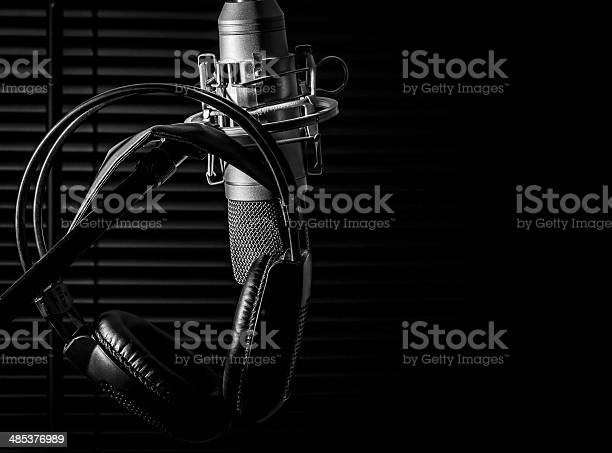 low key image of a condenser microphone on a boom stand, with black headphones in a dark studio, vocal booth. shot taken with a nikon d7000 dslr camera, very sharp image