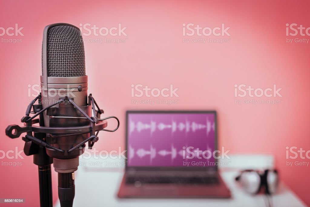 condenser microphone on laptop computer with waveform on screen and headphone background, home studio & recording concept stock photo