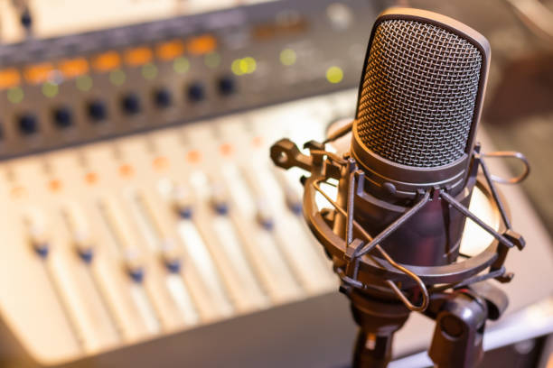 condenser microphone on mixing console background. audio recording concept condenser microphone on mixing console background. audio recording concept analogue audio storage media stock pictures, royalty-free photos & images