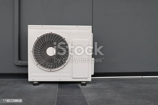 871063730istockphoto Condensing unit of air conditioning systems. Condensing unit installed on the gray wall. 1160239808