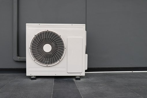 istock Condensing unit of air conditioning systems. Condensing unit installed on the gray wall. 1160239808