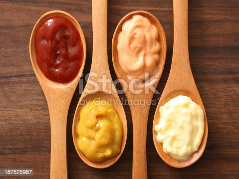 Four spoons with varieties of condiments