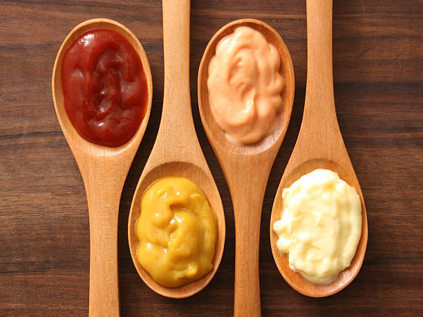 Condiments and spoons stock photo
