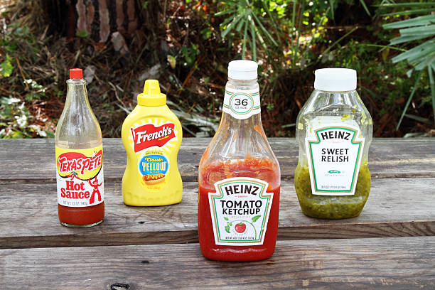 condiments on picnic table. - heinz stock photos and pictures