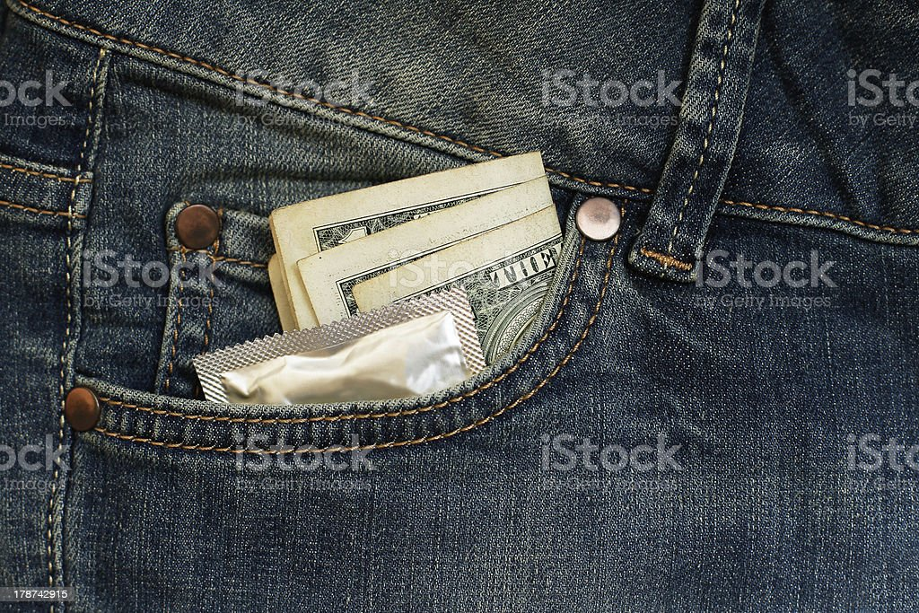 Condom and three dollars in the pocket jeans royalty-free stock photo