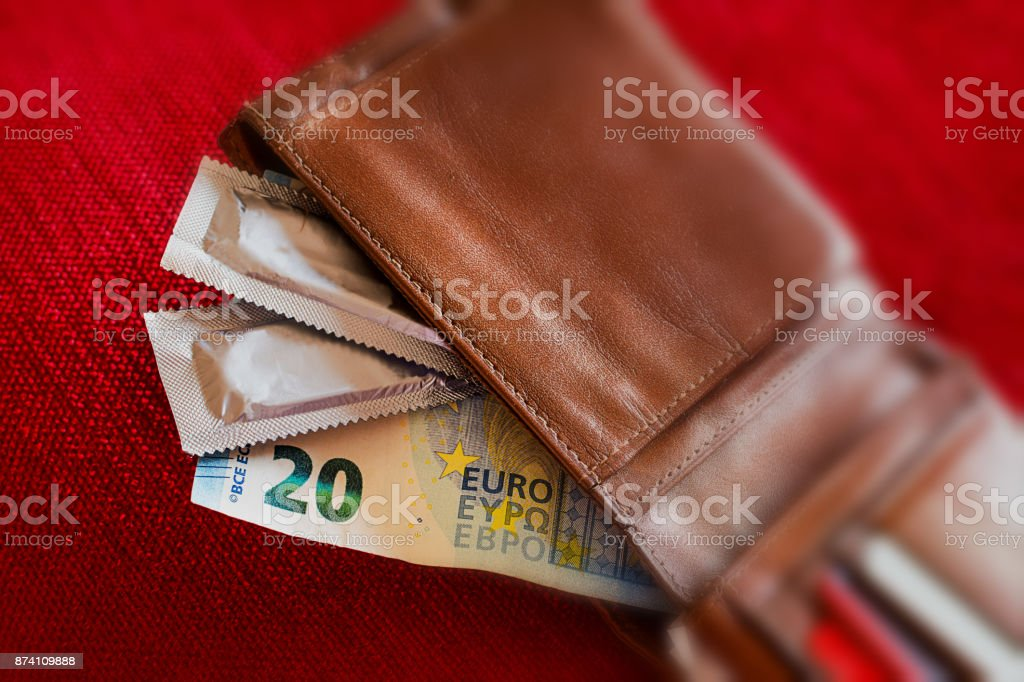Condoms and banknotes in the leather wallet