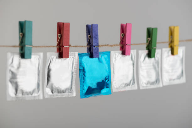condoms hanging on the rope on gray background. - spermicide stock photos and pictures