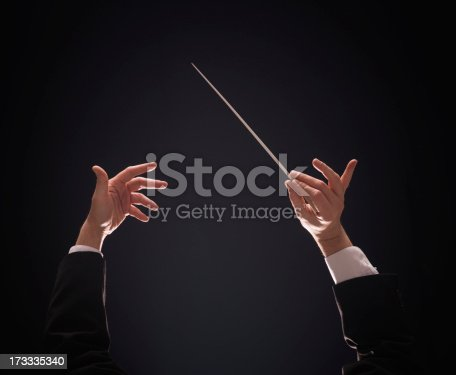Concert conductor hands with baton over dark background