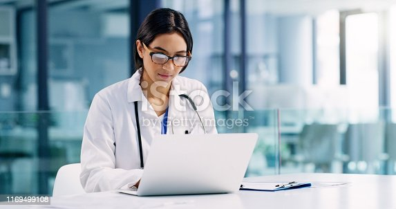 Shot of a young doctor using a laptop in a hospital