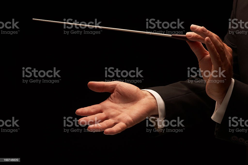 Conductor conducting an orchestra stock photo