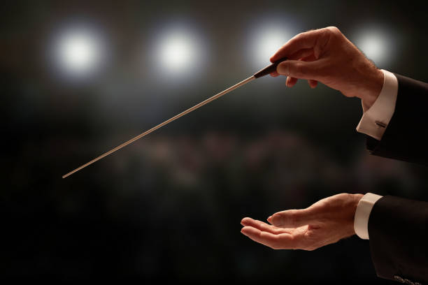 conductor conducting an orchestra - opera stock photos and pictures