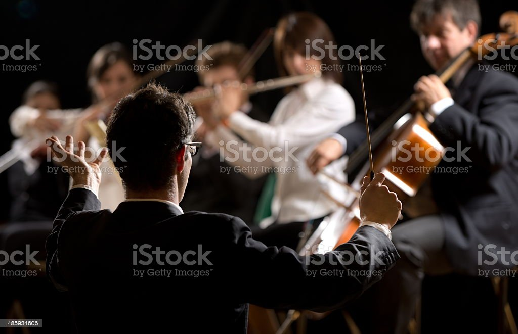 Conductor directing symphony orchestra stock photo