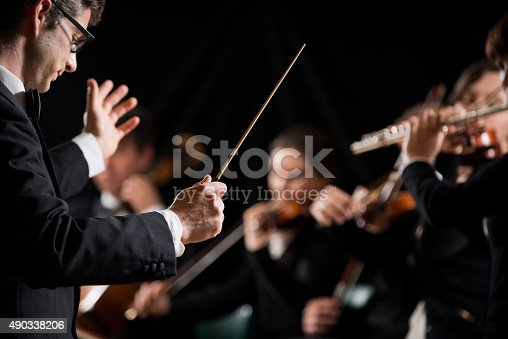 Conductor directing symphony orchestra with performers on background.