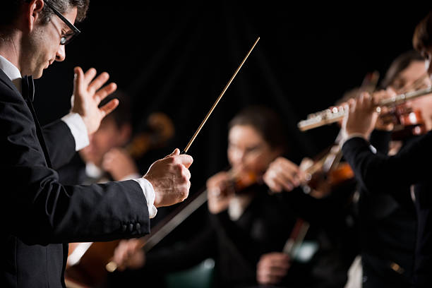 conductor directing symphony orchestra - classical stock photos and pictures