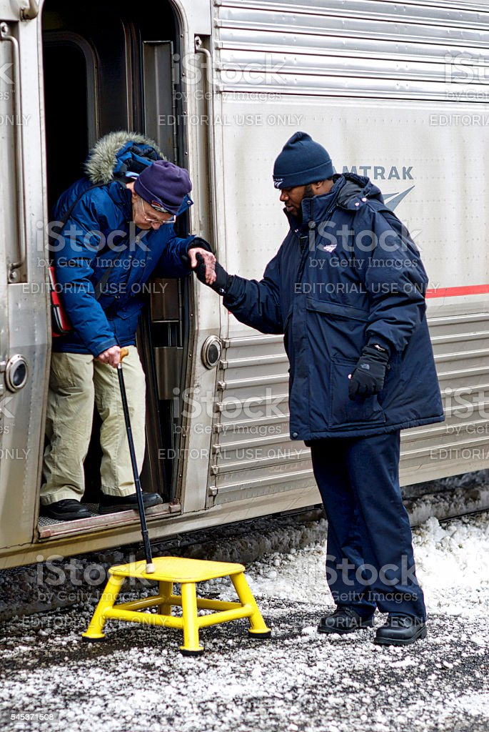 Conductor helps Amtrak passenger stock photo