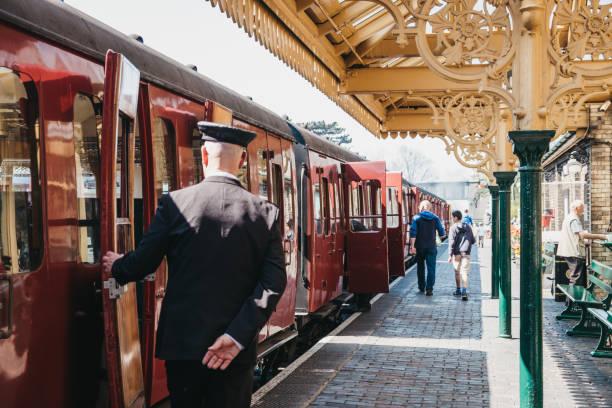 在英國諾福克郡的謝林厄姆站, 列警服關閉復古罌粟線蒸汽列車車門的指揮。 - 火車站月台 個照片及圖片檔