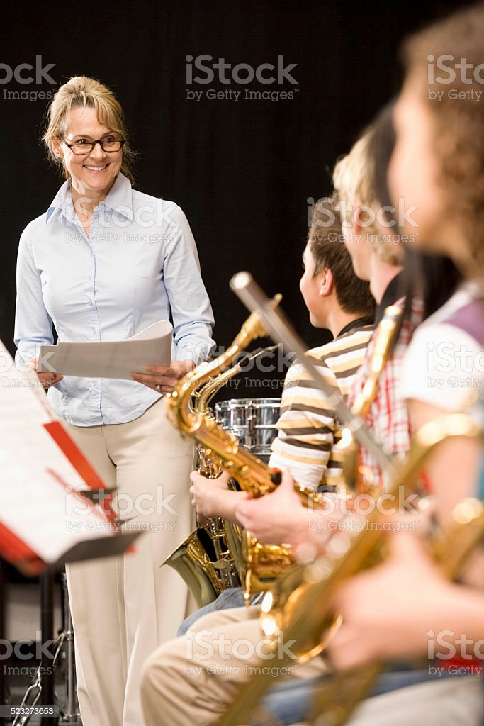 Conductor smiling at high-school music class stock photo