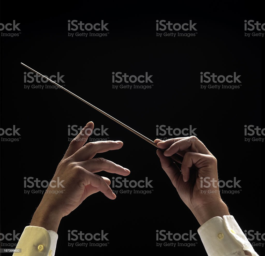 Conductors hands with baton on black background stock photo