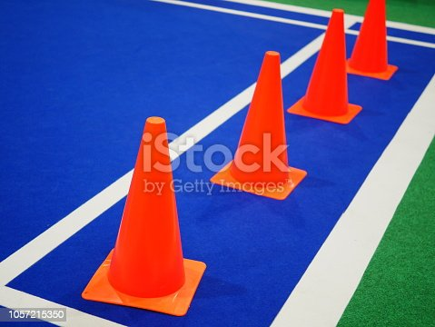 986840244istockphoto Cone markers on the green grass playground 1057215350