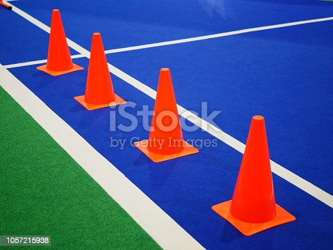 986840244istockphoto Cone markers on the green grass playground 1057215938
