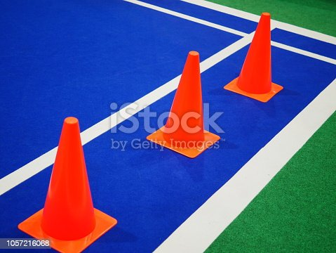 986840244istockphoto Cone markers on the green grass playground 1057216068