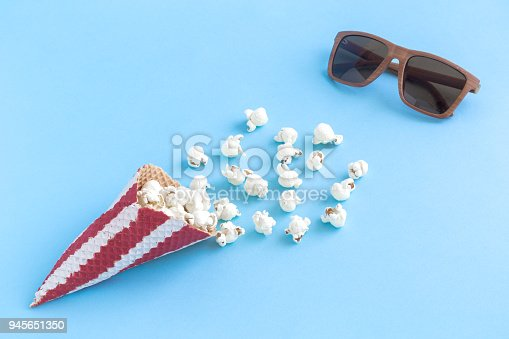 956942702 istock photo Cone with popcorn and movie theater eyeglasses on blue background minimalistic concept. 945651350