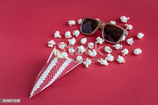 956942702 istock photo Cone with popcorn and movie theater eyeglasses on red background minimalistic concept. 945651538