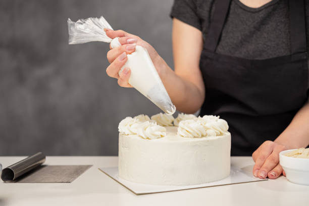 Confectioner at work. Cream cake decorating. Cook table preparing a cake. Confectioner at work. Cream cake decorating. Cook table preparing a cake on a gray background. decorating a cake stock pictures, royalty-free photos & images
