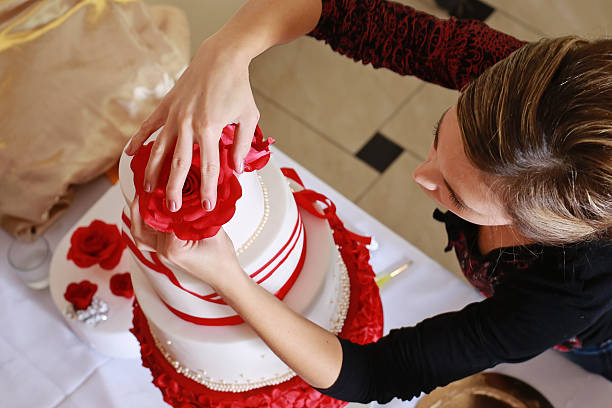 Confectioner decorating a wedding cake with marzipan flowers Confectioner stacking a 4 tier wedding cake at the reception place and decorating it with edible red marzipan flowers decorating a cake stock pictures, royalty-free photos & images