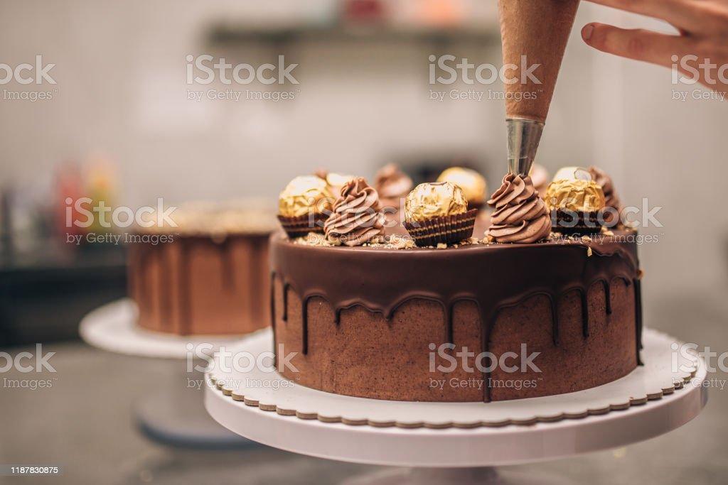 Confectioner decorating chocolate cake, close-up. - Стоковые фото Выпекать роялти-фри