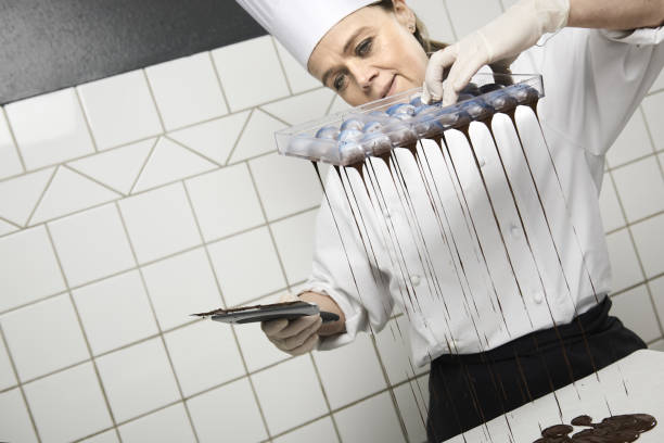 confectioner making cakes and chocolate in her confectionery stock photo