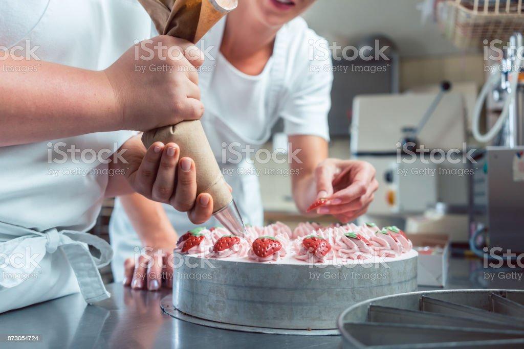 Konditor oder Gebäck Köche schlichten Kuchen mit Spritzbeutel – Foto