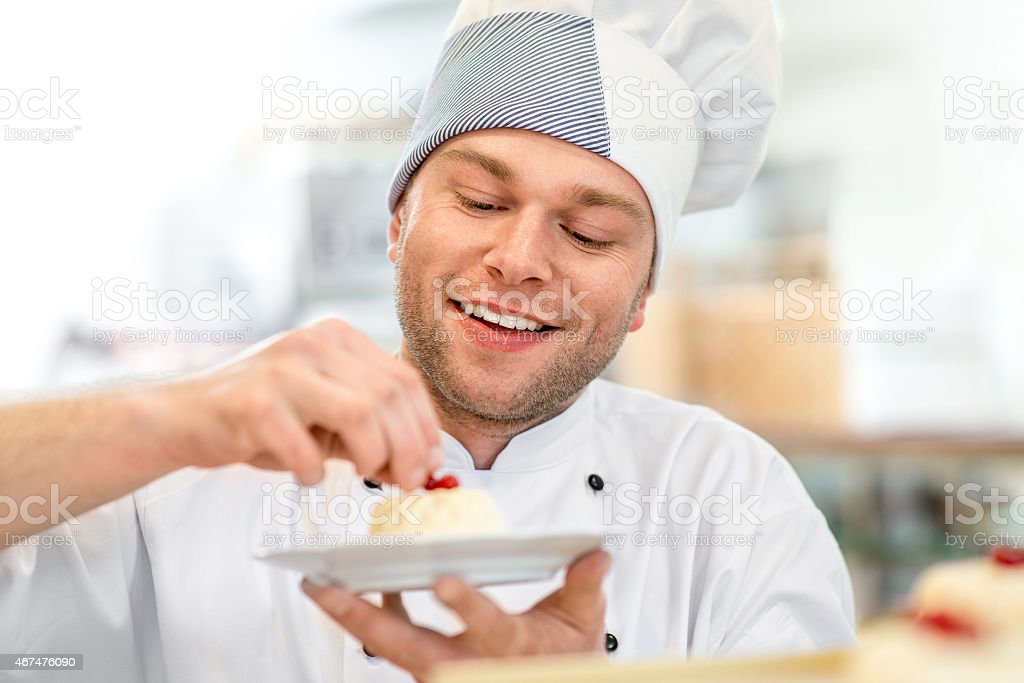 Confectioner putting the final touches onto a cake stock photo