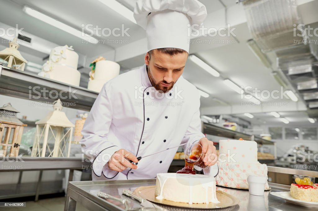 A confectioner with a cake in the bakery stock photo