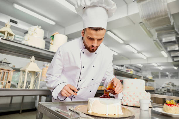 Um pasteleiro com um bolo na padaria - foto de acervo