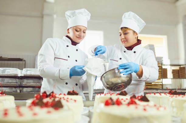 Konditor mit Konditorei in der Hand in der Bäckerei. – Foto